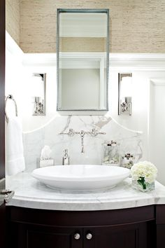Beautiful and elegant bathroom design with sand grasscloth walls and white paneled half wall. Chic beaded mirror and stylish Urban Archaeology Loft Light Sconces hang above an incredible espresso bathroom vanity with carrara marble countertop and white vessel sink against marble backsplash. Exquisite details in polished nickel wall-mount bridge faucet, and hardware.
