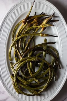 Oven Roasted Garlic Scapes - drizzled with olive oil and sprinkled with salt and pepper then roasted to perfection for a beautiful and whimsical summer side dish. Recipe For Garlic Scapes, Scape Recipe, Roasting Garlic In Oven, Oven Roast, Baked Garlic, Roasted Garlic, Vegetable Sides, Vegetable Recipes, How To Cook Garlic