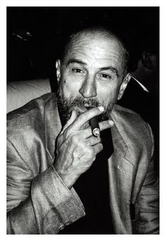 Robert De Niro, smoking a cigar and photographed by Rpxanne Lowit (1996)