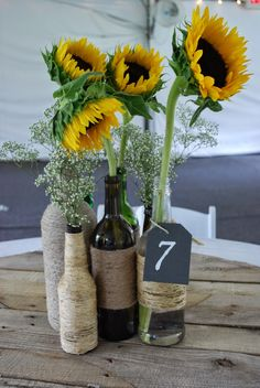 Simple #DIYCenterpieces for a #summer #wedding - #sunflowers in twine wrapped wine bottles