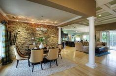 Beautiful stone wall in dining room - track lighting and candles on the wall.  Charming!