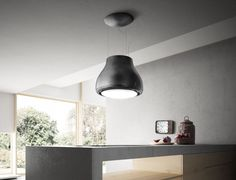 Kitchen Design Idea - Hide The Range Hood | This range hood is surrounded by a light fixture. A charcoal filter filters out the smoke, odors, and steam, purifying the air as it flows out the top.