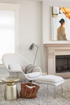 Neutral living room with gold stool, modern lamp, and neutral lounge chair…