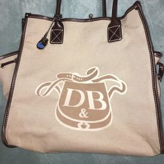 Dooney & Burke Tote Authentic Dooney & Burke tan and brown large tote bag with two side pockets. This is great for large carries such as laptops, books, etc. Dooney & Bourke Bags Totes