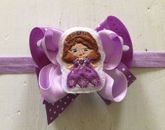 You are looking at a Sophia attached to a double purple boutique hair bow. Its a 3.5 purple polka dot and lavender double boutique bow attached to a