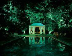 trees lit at night, a tent, a dark still pool. Perfect.