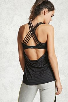 An athletic stretch-knit twofer top featuring a semi-sheer tank top with mesh stripes, scoop neckline and back, and a built-in bra with removable padded cups, and a crisscross strappy back.