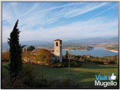 La chiesa di San Giovanni in Petronio a Barberino di Mugello, con il lago di Bilancino sullo sfondo