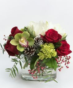 Snowflake - A collection of roses, amaryllis and orchids in shades of green, red, and white is gathered in our oval glass vase with simple seasonal accents.