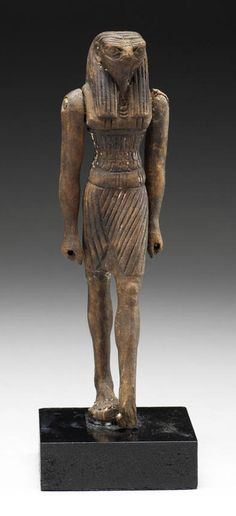 An Egyptian wood figure of Montu  New Kingdom, circa 1550-1070 B.C. The falcon-headed god of war depicted striding, with his left leg advanced, wearing a short kilt and a scalloped tunic, the lappets of his striped tripartite wig falling over his broad collar, his right fist clenched to hold an attribute, now missing, a hole in the top of the wig for insertion of a crown, now missing, 6in (15.2cm) high, mounted