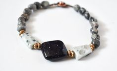 This Designs by s.e.K bracelet features a diamond shaped blue goldstone, surrounded by sesame jasper, brushed brass, and silver crazy lace agate beads, closed with an antique copper-plated brass button clasp.