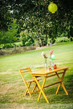 Houten tafeltje en stoeltje met lieve bloemen ter decoratie en natuurlijk als rustpunt voor de gasten van deze tuinbruiloft.