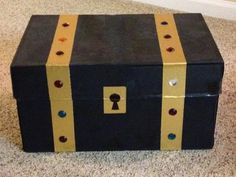 """This is our """"Treasure Chest."""" It's really a copy paper box that's painted black, with gold duct tape and craft jewels. I stock it with season-appropriate goodies as rewards for good behavior on stay-home days. It always has books and sometimes chocolates. It's a good reminder for our boys in reinforcing positive behavior. """"Do we want to have a Treasure Chest day today?"""" is what I ask in the morning, and the box stays hidden until it's time to get to pick a prize."""