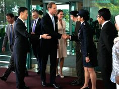 Prince William and his wife, Kate, Duchess of Cambridge, center, are greeted as they arrive at the VIP terminal of Changi International Airport on Sept. 11, 2012, in Singapore. The British royal couple is on an official three-day trip to Singapore.