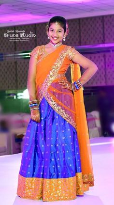 The gorgeous girl wearing blue and light orange half saree, Pure silk lehenga with printed flowers adorned orange border, Gold zari print. Half Saree Designs, Saree Blouse Neck Designs, Saree Blouse Patterns, Lehenga Designs, Half Saree Lehenga, Lehnga Dress, Bridal Lehenga Choli, Silk Lehenga, Frocks For Girls