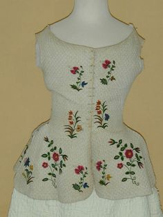 "Embroidered quilted vest, c. 1740's. Quilted undergarments were a popular way to stay warm in the 18th C. Vests like this one, known as ""jumps"", were also used as a foundation garment, worn in place of stays (corsets) in informal situations."