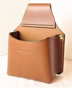Sturdy construction shotgun cartridge box belt holder, versatile little belt holder designed to hold a standard box of cartridge shells, English saddle tan coloured leather.Tear the lid from a box of shells and drop into pouch and away you go.