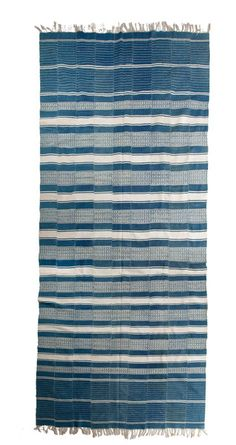 This vintage African indigo textile was hand-dyed and hand-woven in very long strips then hand sew together to make this blanket or rug. It is the weight of a Dhurrie rug. Beautiful varying shades of faded indigo and cream.