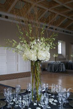 Tall white centerpiece, hydrangea, willow and orchids - switch out the white dendrobiums for gold or orange mokaras for a fall centerpiece.