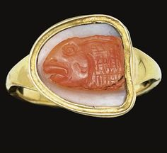A ROMAN FRAGMENTARY AGATE CAMEO   CIRCA 3RD-4TH CENTURY A.D.   Carved in two layers, orange on white, preserving the forepart of a fish, possibly a red mullet, the eyes, mouth, and scales naturalistically rendered; mounted as a ring in a modern gold setting  ½ in. (1.3 cm.) long; ring size 9½