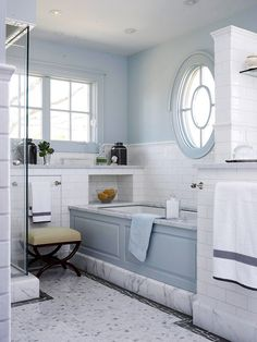 Bath 3 - Adorned with glossy white subway tile and Carrara marble this beautiful bathroom has a Neo-vintage vibe.  Marble is everywhere it seems: in the shower, on the tub deck, base details, countertops, and as small mosaics on the floor. A finely crafted oval window with incredible detailing becomes the focal point of the bath wall.  The soft blue hue carries through from the adjoining bedroom.  A beautiful, finely detailed, finely crafted bathroom. Who couldn't <3 this dream bath?  #bhg.com