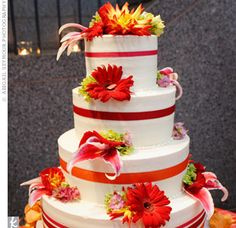 The four-tiered cake was iced in vanilla buttercream with fresh flowers and grosgrain ribbons wrapped around each layer. Two of the four layers were flavored with white cake filled with strawberries and vanilla mousse, while the other two consisted of chocolate cake filled with rich chocolate mousse.