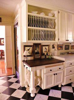 Plate Racks.  Black & white flooring. Art. White Kitchen.