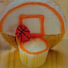 March madness cupcake.  Ice half a sugar cookie, pipe on details and attach the cupcake and cookie with a dap of icing. Let the treat set for at least a half hour before standing them up.