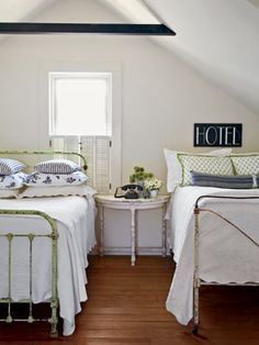 This attic room with twin beds is a perfect hideaway for a guest room. Furniture is kept simple with vintage bed frames and an antique side table. Pillows made from tea towels and a vintage phone and hotel sign add character. Home Bedroom, Bedroom Decor, Budget Bedroom, Bedroom Ideas, Design Bedroom, Attic Design, Bedroom Inspiration, Master Bedroom, Cama Vintage