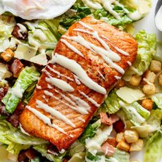 Crispy pan fried Salmon meets Caesar salad for a twist on the traditional! Easy to make with creamy avocado slices, crunchy croutons, the tang of shaved parmesan cheese, a perfect runny poached egg on top and a lightened up Caesar dressing!  http://cafedleites.com