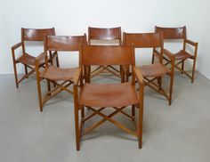 "Mogen Koch - This set of six folding chairs was produced in Denmark in a design reminiscent of the ""Safari"" chair by Mogen Koch. They are made from folding oak frames and are upholstered in cognac colored leather with brass details on the armrests. (Design Period: 1920 to 1949)"