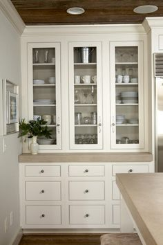 Built-in china cabinet but glass doors-- and more contemporary hardware. White kitchen.