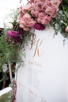 Featuring the couple's gradated gold foil monogram, the seating chart was framed by a bounty of roses, peonies, and greenery.   Photo by Ryan Graham   Styling by Wedding Concepts   Floral design by Fleur le Cordeur
