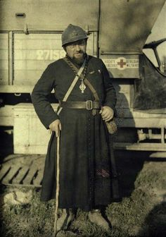 French army chaplain standing in front of a field ambulance, 1917.