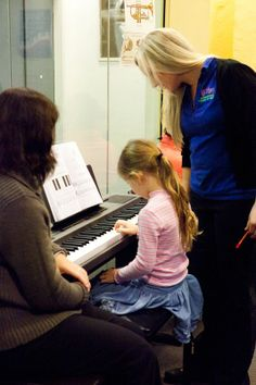 Pianorama primary piano lesson. Teacher helping out the student during piano time