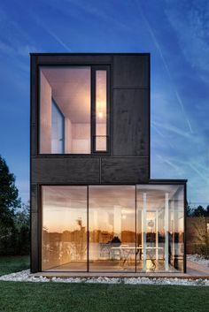 Viel Glas und tiefschwarz lasierte Fassadenplatten aus Okouméholz prägen das Erscheinungsbild