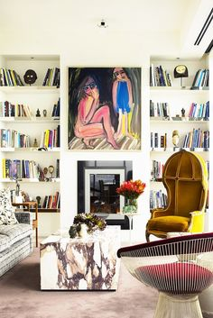 Small library with antique chair and artwork above fireplace