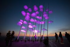 """People stand around """"Umbrellas"""", the sculpture by Giorgos Zogolopoulos, as it is illuminated in pink light to mark the Breast Cancer Awareness Month in Thessaloniki in northern Greece, Oct. 21, 2014."""
