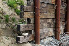 This is a very cool looking design, I love the rusty metal of the pipe and the rustic look of it. hillside retaining walls made of wood - Google Search