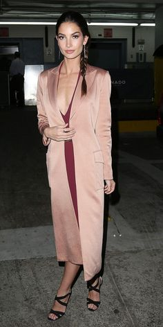 Lily Aldridge wears a sexy low-cut red mini dress with a silky long coat and sleek gold earrings for an evening out