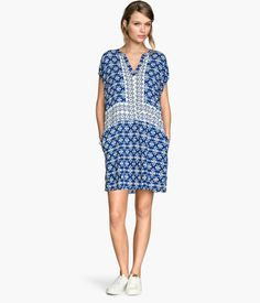Straight-cut dress in woven fabric with a slight sheen. V-neck, seam at waist, side pockets, and slits at sides. Unlined.