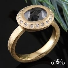Custom 18kt yellow gold, heavy emery finish halo style ring for bezel set oval rose cut black center diamond. Piece has flush set round brilliant cut diamond accent gems.