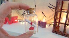MENSAJE EN BOTELLA Materiales que Necesitas: - Un frasquito de cristal con tapón de corcho (el mio era de cuentas de esas para hacer collares, pero también los venden vacios por poco dinero en tiendas de manualidades, en bazares y en tiendas de productos para hacer jabones y cosmeticos) - cartulina - hilo rojo - un pedacito de papel - tijeras - Una grapa o una chincheta plana - y algo para escribir tu mensaje ...... y mucho amor :)
