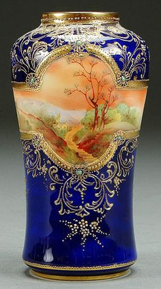 A NIPPON COBALT, JEWELED AND SCENIC DECORATED PORCELAIN VASE CIRCA 1900 WITH AUTUMNAL COUNTRY SCENE AND GILT SCEOLLS ON COBALT GROUND