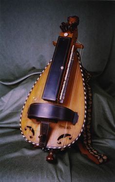 Name HURDY GURDY  Classification Chordophones  'Other name' Entry name: Hurdy gurdy   Vernacular: Viele la roux   Vernacular: Vielle a Roue  'Culture group' French  'Culture group place' France  Description:  Ovoid wood body, flat face, rounded back. Raised integral neck with 6 strings 10 ivory stops braid carry strap metal swing handle at base.  'Associated date' Approx. 19th century AD popularity