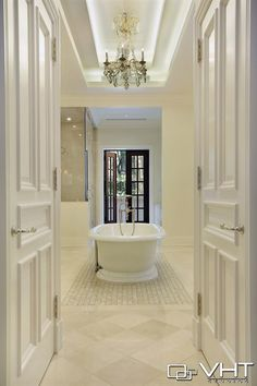 Classy master bathroom with a beautiful chandelier over the bathtub - we love it!