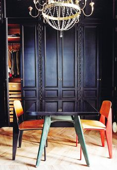 the mix of parquet flooring, mod chairs, dramatic black doors + a glimpse of a glam chandelier contrasts contemporary with tradition