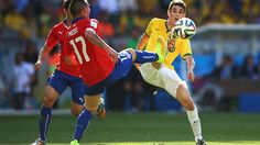 Gary Medel of Chile and Oscar of Brazil compete for the ball