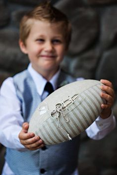 My nephew carried our rings out on a football. Purchased on Etsy. Photos by Atelier Pictures in Portland. #footballwedding #ringbearer #wedding. Sports wedding ideas. Football ring bearer.
