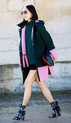 Eva Chen wears a high-neck top, miniskirt, green and pink coat, cat-eye sunglasses, and floral Valentino boots